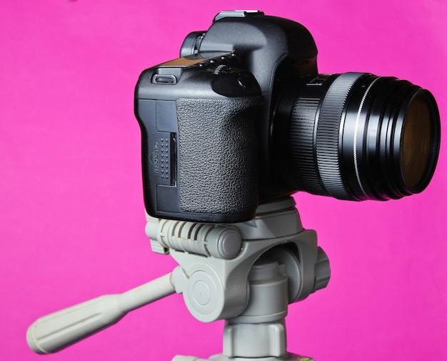 Moderna fotocamera digitale con treppiede sul tavolo rosa.