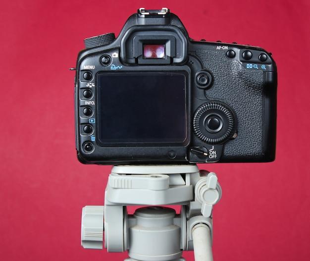 Moderna fotocamera digitale con treppiede sul tavolo rosso.