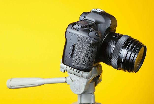 Moderna fotocamera digitale con un treppiede su un tavolo giallo