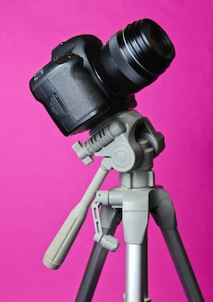 Moderna fotocamera digitale con un treppiede sul tavolo rosa. astrofotografia