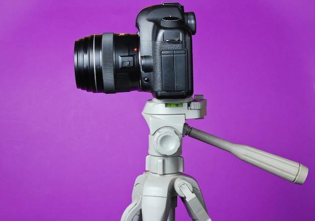 Moderna fotocamera digitale con un treppiede sul tavolo viola. vista frontale