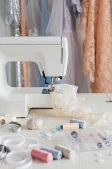 Moderna macchina da cucire con fili sul tavolo