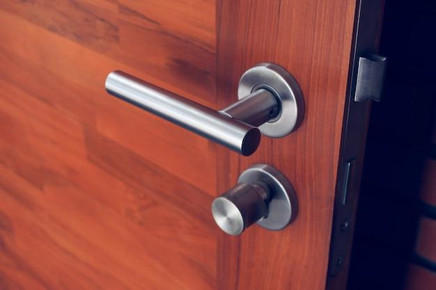 Moderna maniglia per porta in acciaio inox o alluminio su porta in legno