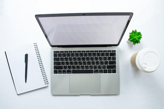 Moderna scrivania bianca con tavolo per laptop, smartphone e altri accessori con pagine di libri per prendere appunti