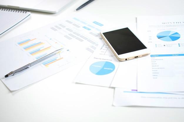 Moderna scrivania bianca sul tavolo con documenti finanziari e un telefono cellulare