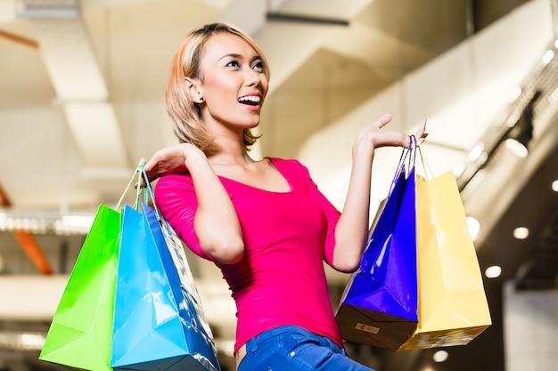 Modo di acquisto asiatico della giovane donna in deposito