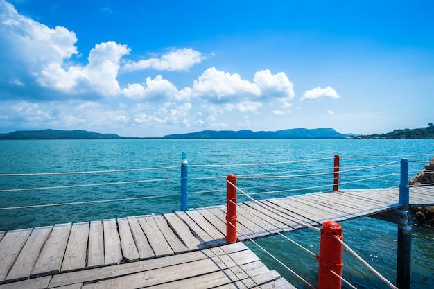 Modo di camminata di legno del ponte nel mare al cielo blu della spiaggia di lao di chao del cappello