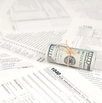 Modulo di dichiarazione dei redditi individuale con rotolo di banconote in dollari