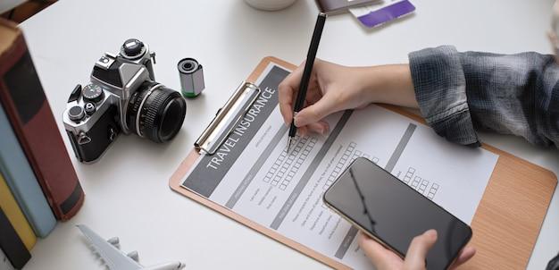 Modulo di riempimento di assicurazione di viaggio femminile mentre guardando il suo piano di viaggio sullo smartphone
