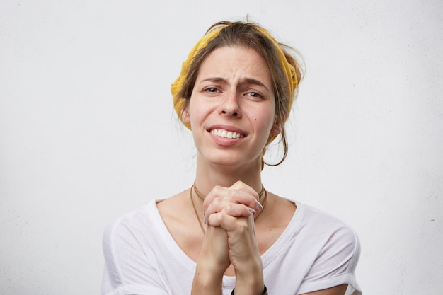 Moglie addolorata che tiene le mani insieme chiedendo e implorando il marito di perdono mentre è colpevole.