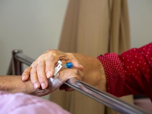 Moglie che visita il marito in ospedale. coppie senior che si tengono per mano sul letto di ospedale