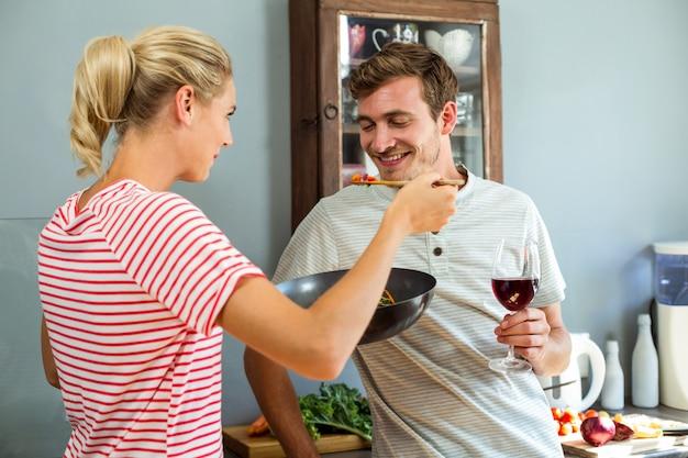 Moglie cucina cibo con il marito in cucina