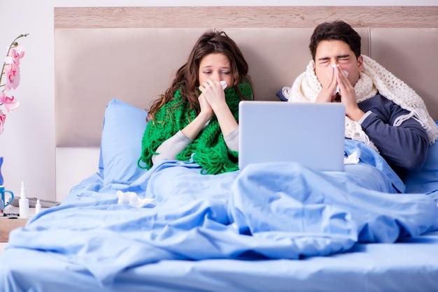 Moglie e marito malati a letto con il computer portatile
