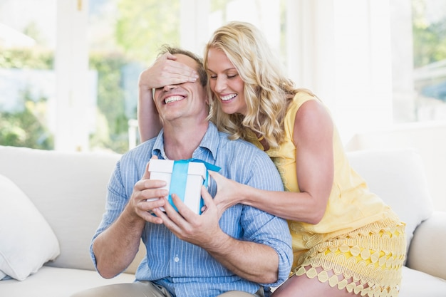 Moglie felice che dà presente al marito nel soggiorno