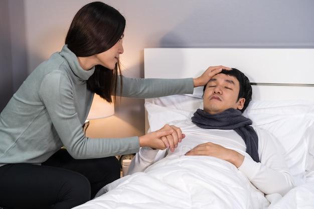 Moglie in visita e prendersi cura del marito malato mentre dorme sul letto di casa