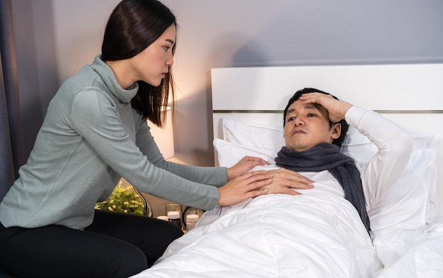 Moglie in visita e prendersi cura del marito malato mentre è sdraiato sul letto a casa