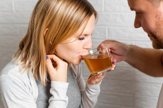 Moglie incinta che beve il tè aiutata da suo marito