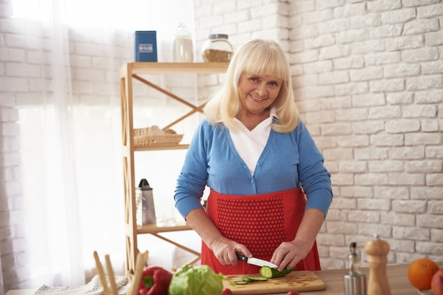 Moglie invecchiata cooking in home dinner preparation.