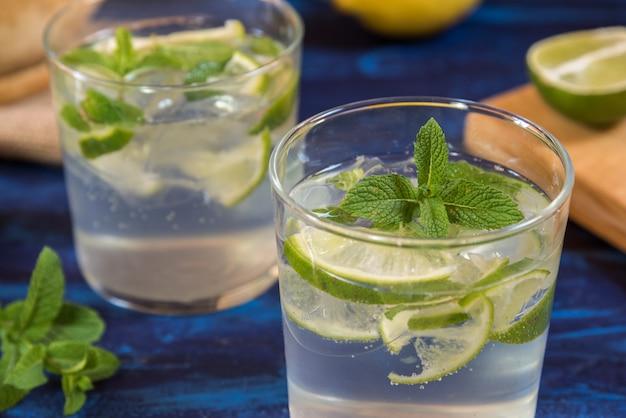 Mojito cocktail con i suoi ingredienti su un tavolo blu
