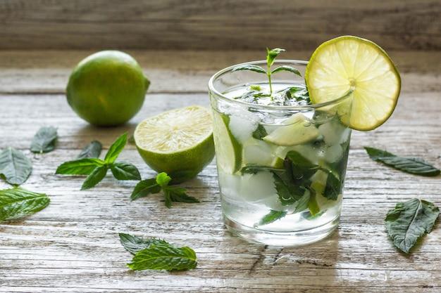 Mojito cocktail con lime e menta nel bicchiere highball su uno sfondo bianco in legno