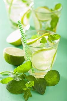 Mojito cocktail e ingredienti sul tavolo verde