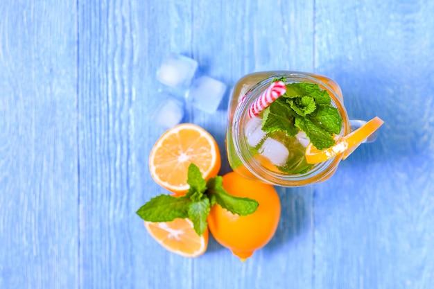 Mojito cocktail estivo con menta, succo di lime, acqua gassata e ghiaccio su un tavolo di legno blu bianco.