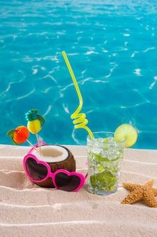 Mojito cocktail sulla spiaggia di sabbia con cocco e occhiali da sole