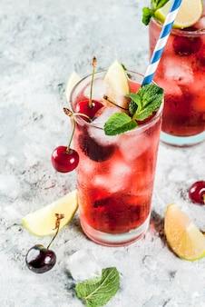 Mojito di ciliegia cola in bicchiere alto con foglie di menta
