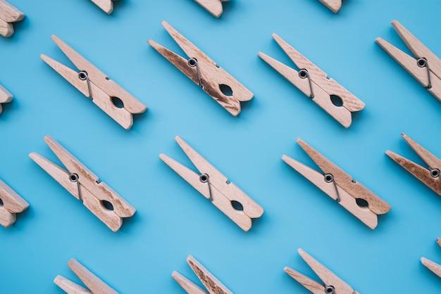 Mollette da bucato di legno di disposizione piana su fondo blu