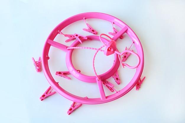 Mollette da bucato di plastica del cerchio rosa su fondo bianco.