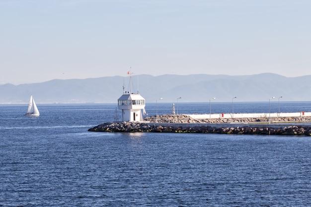 Molo con faro e yacht nel mare del bosforo