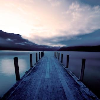 Molo della barca e un lago calmo ad alba, nuova zelanda.