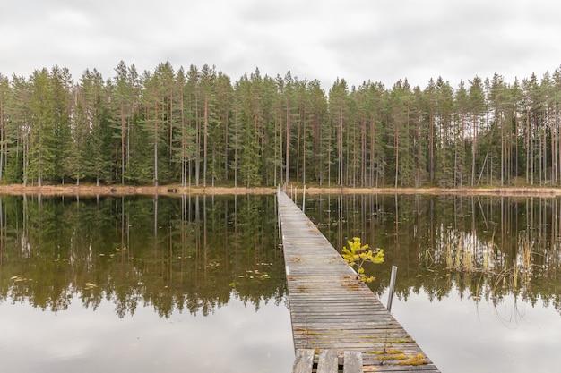 Molo di legno che conduce alla sponda opposta, paesaggio autunnale. svezia.