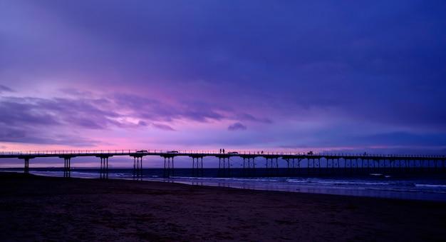 Molo di saltburn in inverno con cielo drammatico di sera, saltburn è una cittadina balneare situata sulla costa nord-orientale del regno unito, prospettiva del ponte di legno verso il mare con riflesso di luce sotto