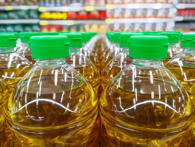 Molte bottiglie in fila pila di olio vegetale sugli scaffali in materiale del supermercato