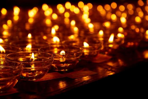 Molte candele accese con poca profondità di campo, candele in una chiesa