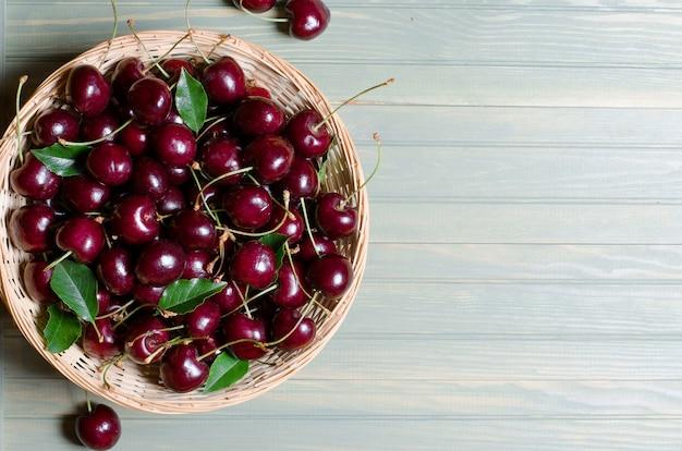 Molte ciliege rosse mature in un cestino di vimini.