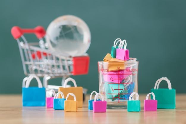 Molte colorate shopping bag in miniatura in tazza di misurazione con carrello e globo
