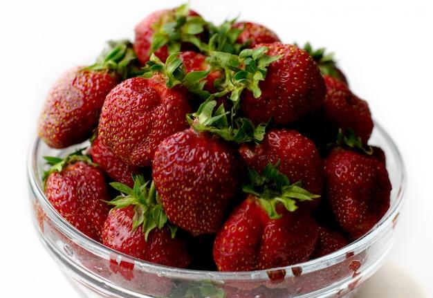 Molte fragole dolci in un piatto trasparente