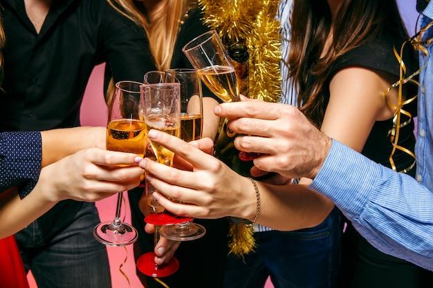 Molte giovani donne e uomini che bevono alla festa di natale