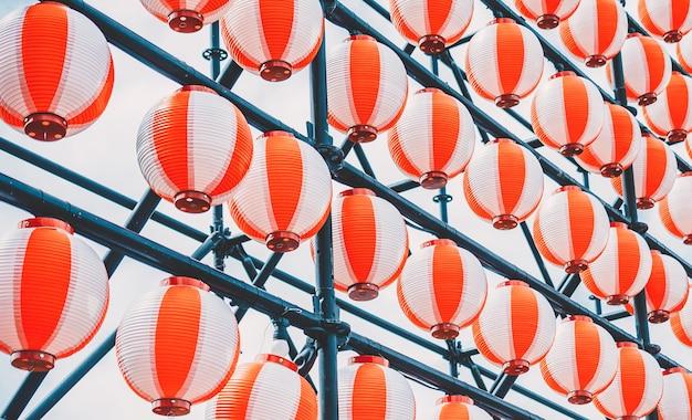 Molte lanterne di carta orientali bianche rosse di carta che appendono in una fila sul cielo blu