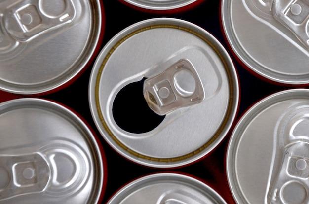Molte lattine di bibite gassate o contenitori per bevande energetiche. molte lattine riciclate realizzate in alluminio e preparate per la ri-produzione.
