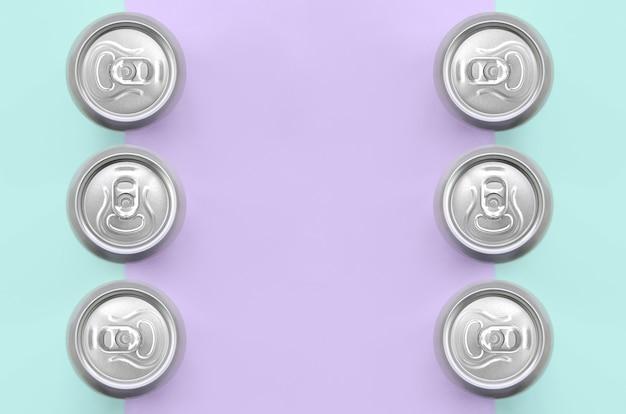Molte lattine di birra metallica di moda pastello viola e carta di colori blu nel concetto minimo