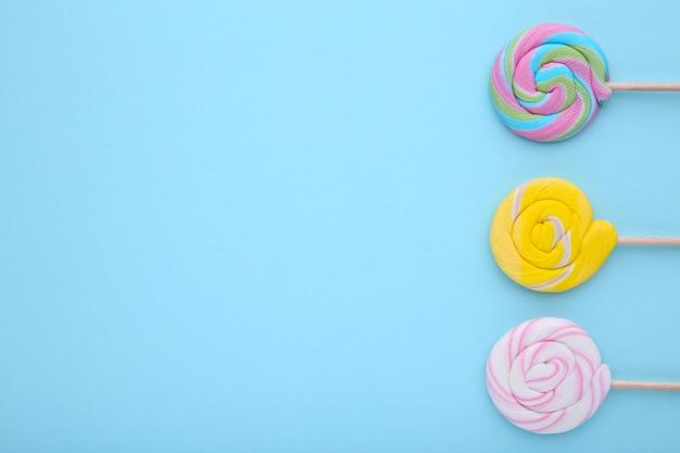 Molte lecca-lecca colorate su sfondo blu, dolci