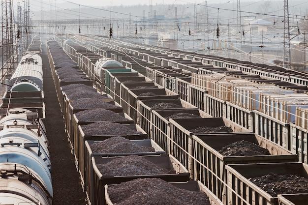 Molte macchine sono sui binari della ferrovia. treni merci. spedizione merci. carbone, assi di legno, ghiaia, pietrisco. carri. trasporto ferroviario.