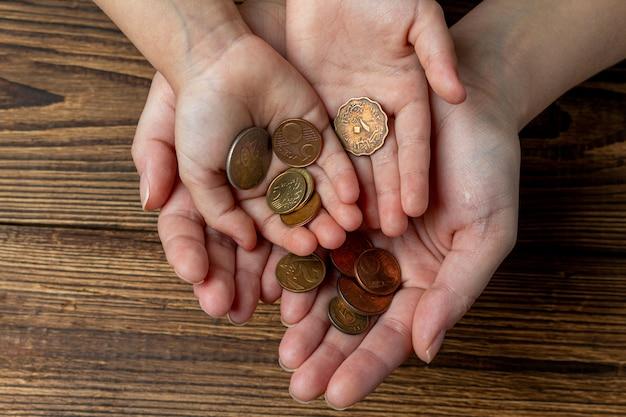 Molte mani che tengono le monete nei palmi. condividi, beneficenza, concetto di famiglia.