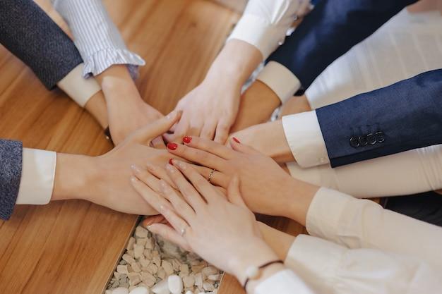 Molte mani di persone in giacca e cravatta in mezzo al tavolo, il lavoro della squadra