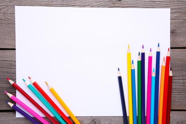 Molte matite colorate differenti con carta bianca su di legno grigio