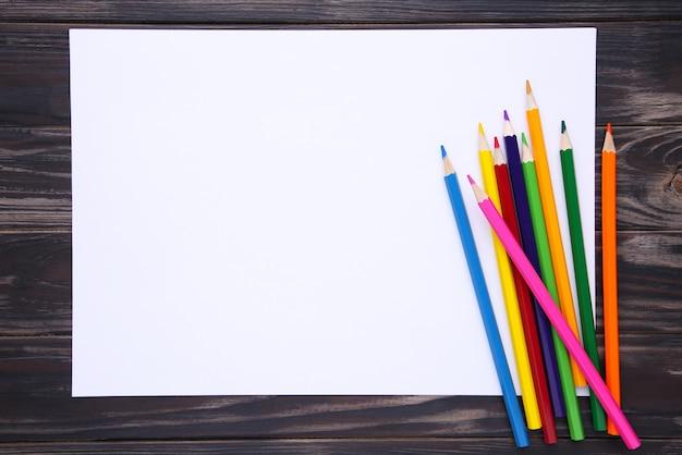 Molte matite colorate differenti con libro bianco su di legno marrone