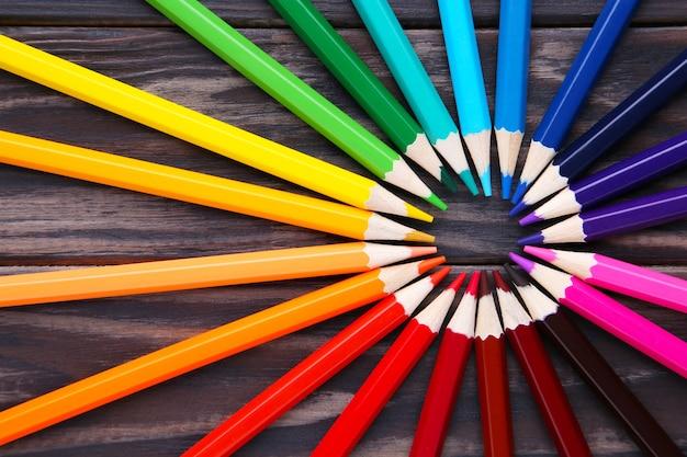 Molte matite colorate differenti su legno marrone